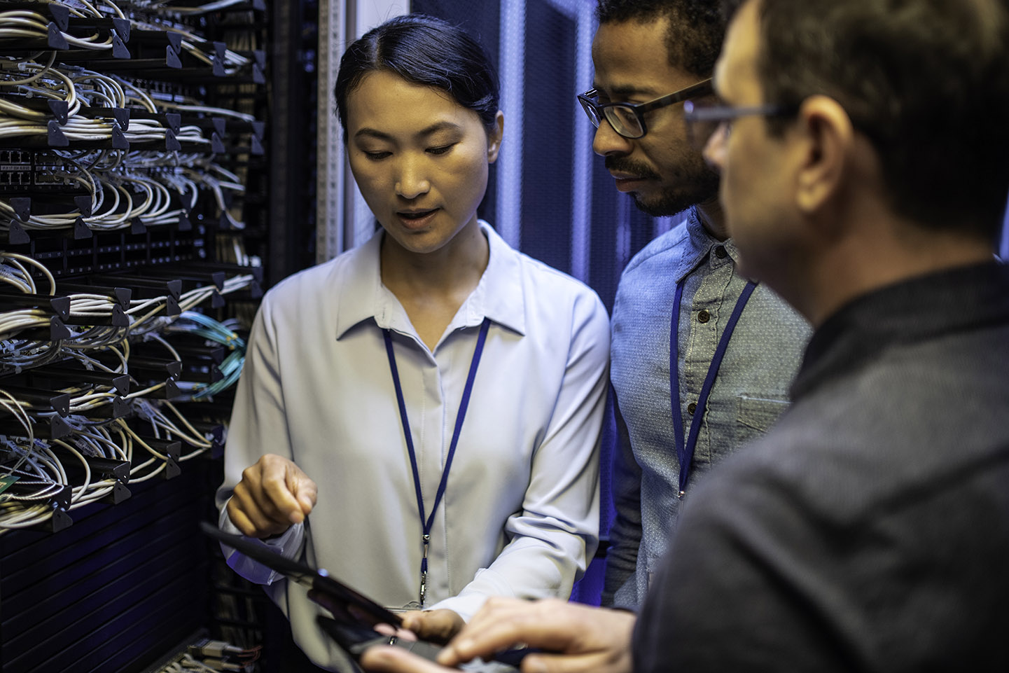 Three IT technician looking at a digital tablet and talking while standing next to a server in a data center.
