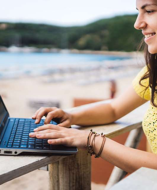 girl working on computer by a beach